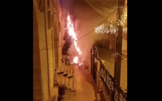 Une capture d'écran d'une vidéo publiée sur les réseaux sociaux montrant un arbre de Noël incendié devant une église dans la ville arabe israélienne de Sakhnin, le 30 décembre 2020. (Capture d'écran : Twitter)