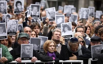 Des personnes en deuil brandissent des photos des victimes de l'attentat à la bombe du centre juif AMIA qui a tué 85 personnes le 18 juillet 2019 à Buenos Aires, en Argentine, à l'occasion du 25e anniversaire de l'attaque. (AP Photo/Natacha Pisarenko)