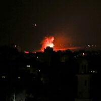 De la fumée et des flammes suite à une frappe aérienne israélienne à Gaza City, après le lancement par les terroristes de roquettes en Israël, le 26 décembre 2020. (Crédit : Mahmud Hams/AFP)