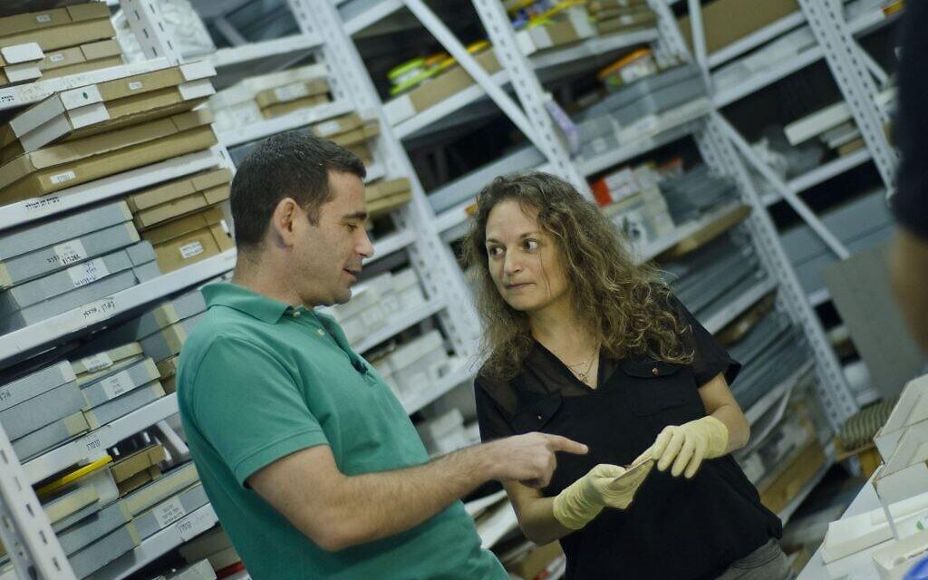 Le docteur Erez Ben-Yosef et la docteure  Naama Sukenik examinent des fragments de textile colorés découverts à Timna. (Crédit : Yolli Schwartz, autorisation de l'Autorité israélienne des antiquités)