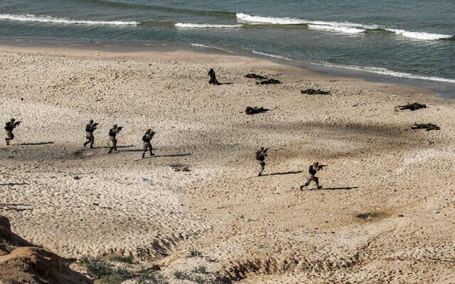 Un exercice militaire du Hamas et d'autres groupes terroristes palestiniens armés sur une plage de la ville de Gaza le 29 décembre 2020. (Crédit   : MOHAMMED ABED / AFP)