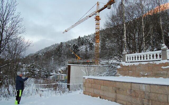 Terje Lien, le plus proche voisin d'Utoyakaia, en Norvège, le 5 janvier 2021, indique le site de construction, où un mémorial est en cours de construction pour honorer les 77 personnes qui ont été tuées le 22 juillet 2011 par l'extrémiste de droite norvégien Anders Behring Breivik, dont 69 sur l'île voisine d'Utoya. (Crédit : Pierre-Henry DESHAYES / AFP)