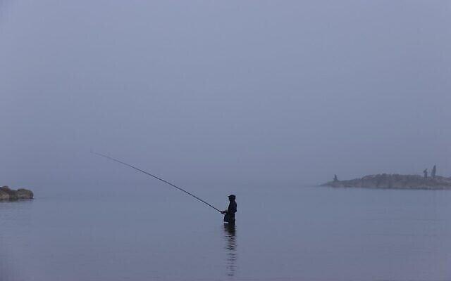 Un homme pêche dans le brouillard matinal dans la ville côtière de Netanya, le 6 janvier 2021. (JACK GUEZ / AFP)