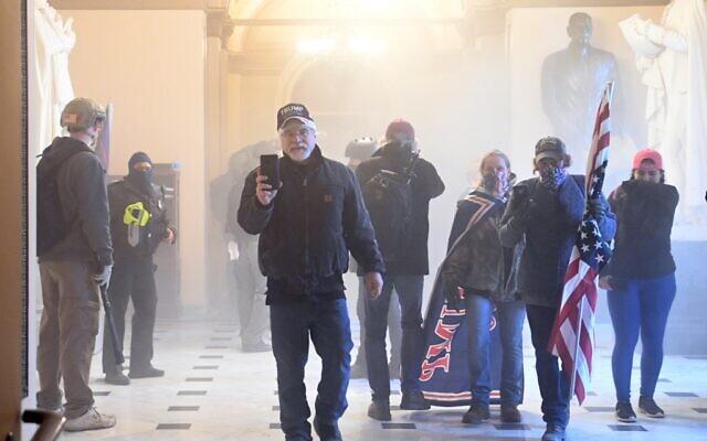 Les partisans du président américain Donald Trump prennent d'assaut le Capitole américain, enfumé par gaz lacrymogènes, le 6 janvier 2021 à Washington, DC. (Crédit : Saul LOEB / AFP)