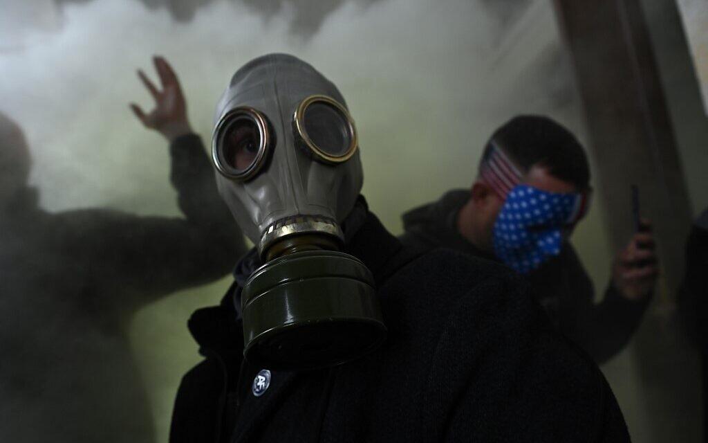 Un partisan du président américain Donald Trump porte un masque à gaz alors qu'il proteste après avoir pris d'assaut le Capitole américain, le 6 janvier 2021, à Washington, DC. (Brendan SMIALOWSKI / AFP)