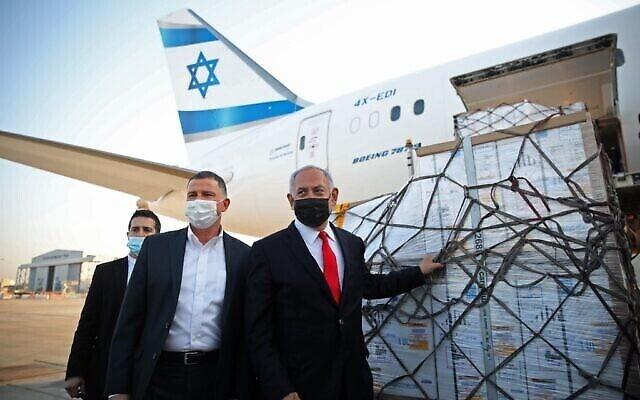 Le Premier ministre israélien Benjamin Netanyahu (à droite) et le ministre de la Santé Yuli Edelstein (à gauche) assistent à une cérémonie pour l'arrivée d'un avion transportant une cargaison de vaccins anti-coronavirus Pfizer-BioNTech, à l'aéroport Ben Gurion près de la ville israélienne de Tel Aviv, le 10 janvier 2021. (Motti MILLROD / POOL / AFP)