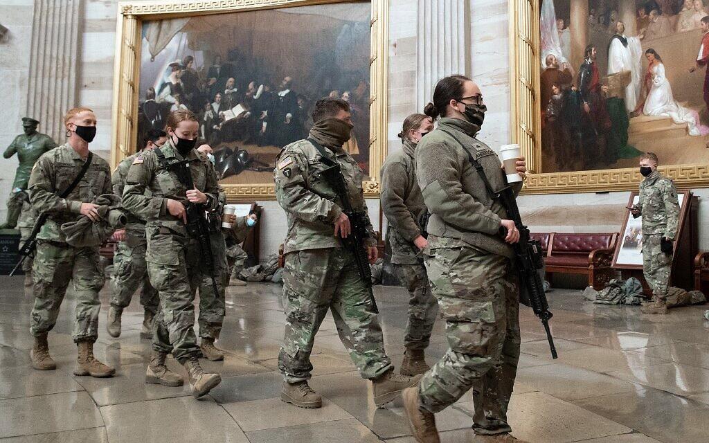 Des membres de la Garde nationale marchent dans la rotonde du Capitole américain à Washington, DC, le 13 janvier 2021, avant le vote de la Chambre des représentants mettant en accusation le président américain Donald Trump. (Saul Loeb / AFP)