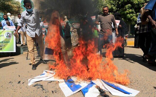 Des manifestants soudanais brûlent des drapeaux israéliens pendant un rassemblement suite à la signature d'un accord de normalisation entre le Soudan et l'Etat juif aux abords des bureaux du cabinet à Khartoum, le 17 janvier 2021. (Crédit :  ASHRAF SHAZLY / AFP)