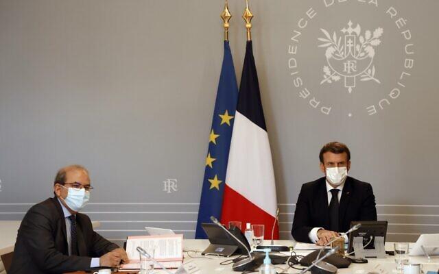 """Mohammed Moussaoui (L), président du Conseil français du culte musulman (CFCM) signe une """"charte de principes"""" aux côtés du président français Emmanuel Macron, le 18 janvier 2021 au palais de l'Elysée à Paris. (Crédit : Ludovic Marin/Pool/AFP)"""
