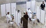 Un voyageur s'adresse à un médecin pour qu'il lui fasse passer un test de dépistage du coronavirus, à son arrivée au centre de dépistage rapide de l'aéroport international Ben-Gurion, près de Tel-Aviv, le 24 janvier 2021. (Crédit : JACK GUEZ / AFP)