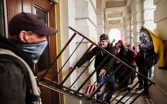 Un membre d'une foule pro-Trump défonce une entrée du Capitole pour tenter d'y accéder le 6 janvier 2021 à Washington, DC. Une foule pro-Trump a pris d'assaut le Capitole, brisant des fenêtres et s'affrontant avec des policiers. (Crédit : Jon Cherry/Getty Images/AFP)