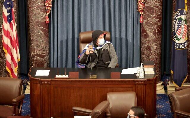 Un manifestant assis dans la salle du Sénat le 6 janvier 2021 à Washington, DC. Le Congrès a tenu une session conjointe aujourd'hui pour ratifier la victoire du Collège électoral 306-232 du Président élu Joe Biden sur le Président Donald Trump. Les manifestants pro-Trump ont pris d'assaut le Capitole américain après les manifestations de masse dans la capitale du pays. (Crédit : Gagner McNamee/Getty Images/AFP)