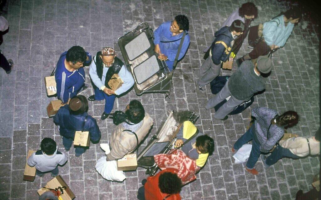 Des Israéliens tenant des boîtes en carton qui renferment des masques à gaz par crainte d'une attaque à l'arme chimique, pendant la première guerre du Golfe de 1991. (Noam Wind / Archives du ministère de la Défense)