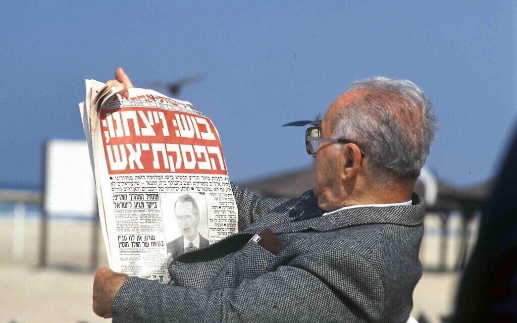 Un homme sur la plage avec un journal dont le titre est : «Bush : Nous avons gagné ; un cessez-le-feu », en référence à la fin de la première guerre du Golfe de 1991. (Archives du ministère de la Défense)