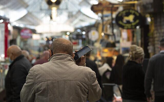 Un homme parle au téléphone au marché Mahane Yehuda à Jérusalem, le 23 décembre 2020. (Crédit : Maya Alleruzzo / AP)