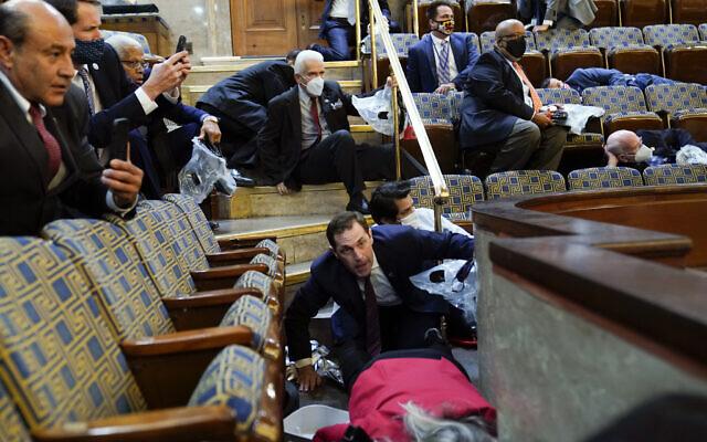 Des gens s'abritent dans la galerie de la Chambre des représentants alors que des manifestants tentent de s'introduire dans l'hémicycle du Capitole américain, le mercredi 6 janvier 2021, à Washington. (AP Photo/Andrew Harnik)