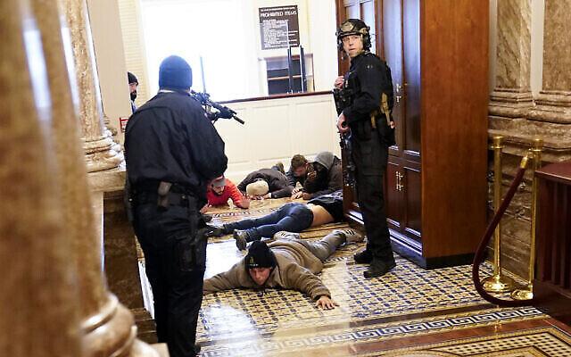 La police du Capitole américain tient des manifestants sous la menace d'une arme à feu près de la Chambre des représentants, à l'intérieur du Capitole américain, le mercredi 6 janvier 2021, à Washington.  (Crédit : AP Photo/Andrew Harnik)