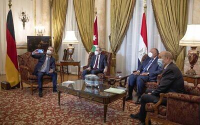 De gauche à droite, le ministre allemand des Affaires étrangères Heiko Maas, prend une photo de journalistes avec son téléphone portable, lors d'une réunion avec le ministre jordanien des Affaires étrangères Ayman Safadi, le ministre égyptien des Affaires étrangères Sameh Shoukry, et le ministre français des Affaires étrangères Jean-Yves Le Drian, avant une conférence de presse au Palais Tahrir, au Caire, en Égypte, le 11 janvier 2021. (AP Photo/Nariman El-Mofty)