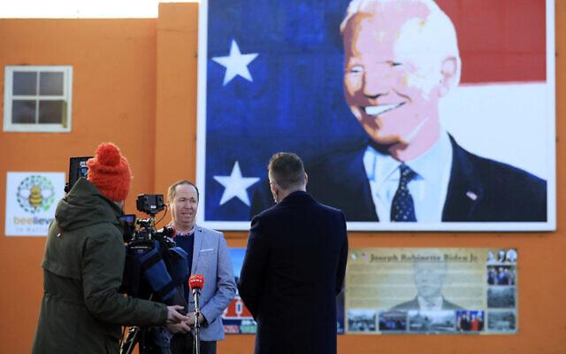 Le cousin de Joe Biden, Joe Blewitt, parle aux médias sous une fresque de Joe Biden peintes sur un mur de Ballina, en Irlande, le 20 janvier 2021. (Crédit :  AP Photo/Peter Morrison)