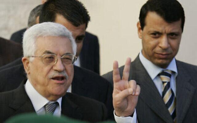 Le président de l'Autorité palestinienne Mahmoud Abbas (à gauche) fait le signe V de la victoire alors que le leader du Fatah Mohammed Dahlan (à droite) assiste à leur rencontre avec le Premier ministre britannique Tony Blair dans son bureau de Ramallah, en Cisjordanie, le 18 décembre 2006. (AP Photo/Kevin Frayer/File)