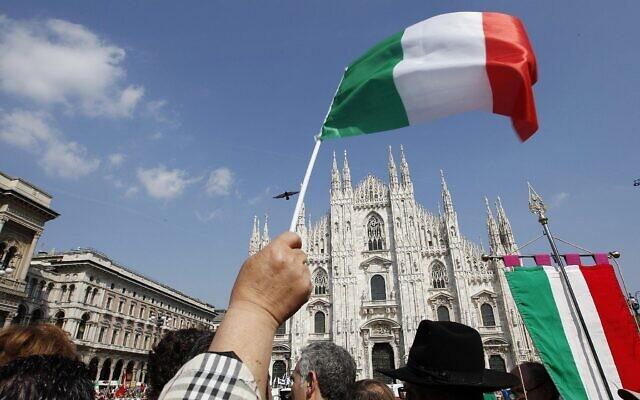 Un homme brandit un drapeau italien devant la cathédrale gothique de Milan, en Italie, à l'occasion de la Journée de la libération, le dimanche 25 avril 2010. (Crédit ; AP Photo/Luca Bruno)