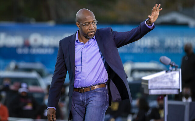 Le candidat démocrate au sénat  Raphael Warnock salue ses partisans pendant un rassemblement organisé à Savannah, en Georgie, le 3 janvier 2021. (Crédit : AP Photo/Stephen B. Morton)