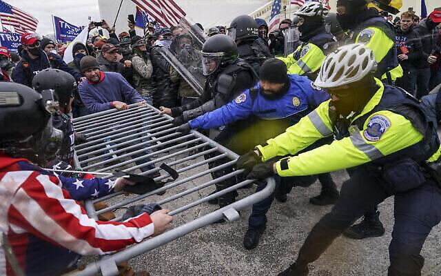 Des partisans de Trump tentent de franchir une barrière policière, le 6 janvier 2021, au Capitole de Washington. Alors que le Congrès s'apprête à affirmer la victoire du président élu Joe Biden, des milliers de personnes se sont rassemblées pour montrer leur soutien au président Donald Trump et à ses accusations de fraude électorale (Crédit : AP Photo/John Minchillo).