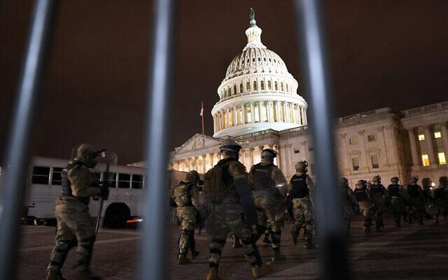 Des membres de la Garde nationale arrivent pour sécuriser la zone située à l'extérieur du Capitole américain, le 6 janvier 2021, à Washington. (Crédit : AP Photo/Jacquelyn Martin)