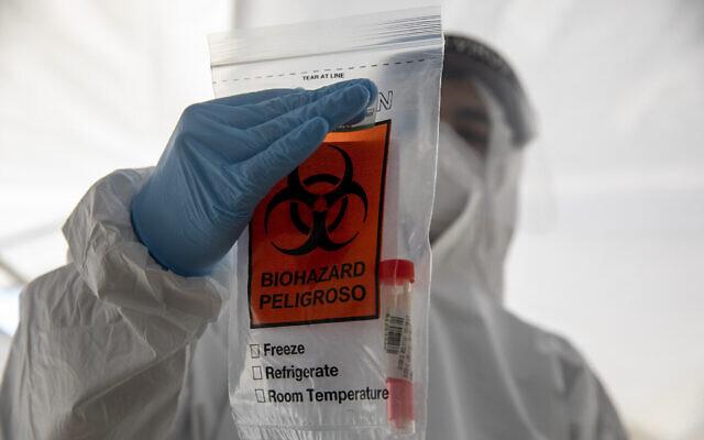 Un professionnel de santé israélien tient un échantillon de test COVID-19 dans un sac dans un centre de test à Jérusalem pendant un confinement national pour freiner la propagation du coronavirus, le 10 janvier 2021. (AP Photo/Ariel Schalit)