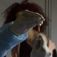Un professionnel de la santé prépare une dose du vaccin COVID-19 de Pfizer dans un centre de vaccination provisoire dans un stade de Jérusalem, le 14 janvier 2021. (AP Photo / Maya Alleruzzo)