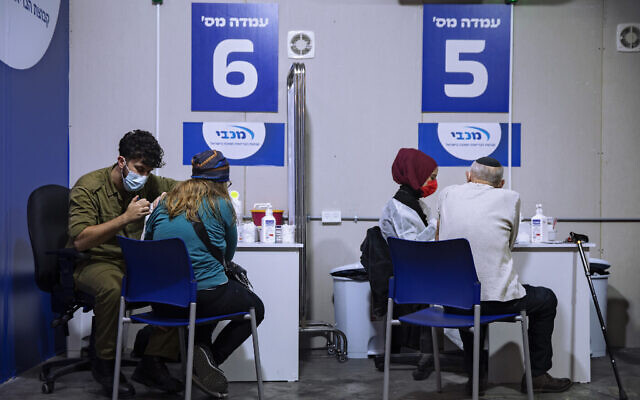 Une femme reçoit son deuxième vaccin Pfizer-BioNTech COVID-19 par un médecin de l'armée, (à gauche), dans un centre de vaccination installé sur le parking d'un centre commercial à Givataim, dans le centre d'Israël, au cours d'un confinement national visant à enrayer la propagation du virus, le 20 janvier 2021. (AP Photo/Oded Balilty)