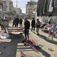 Des civils et des forces de sécurité sur le site d'un attentat à la bombe dans la zone commerciale animée de Bagdad, en Irak, le 21 janvier 2021. (AP Photo / Hadi Mizban)