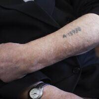 Un survivant de la Shoah montre son numéro de prisonnier tatoué sur son bras. (Crédit :  Yonatan Sindel/Flash90)
