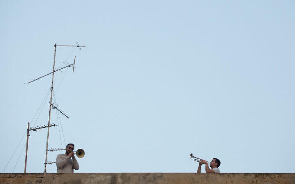Les Israéliens écoutent depuis leur balcon le saxophoniste Yarden Klayman lors d'un concert donné sur un toit de la place Basel à Tel Aviv, le 23 mars 2020. (Crédit : Miriam Alster/Flash90)