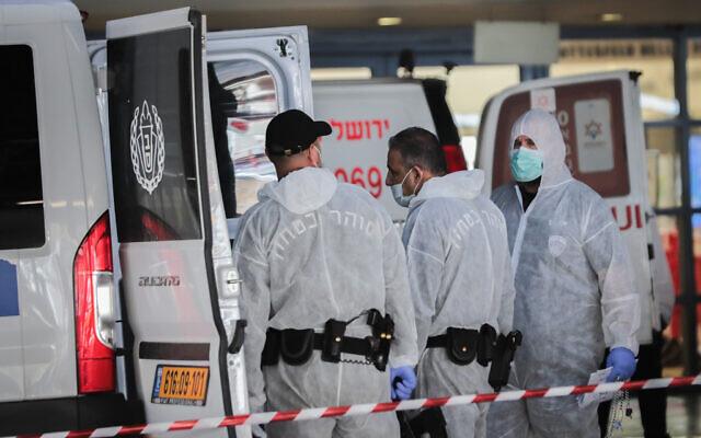Gardes de prison portant des vêtements de protection à titre préventif contre le coronavirus, vus lors du transport d'un prisonnier suspecté d'être atteint du coronavirus au centre médical Shaare Zedek à Jérusalem, le 30 mars 2020. (Yossi Zamir/Flash90)
