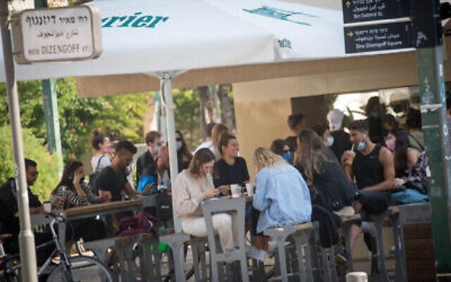 Des Israéliens sont assis dans un café à Tel Aviv, le 2 décembre 2020. (Miriam Alster/Flash90)