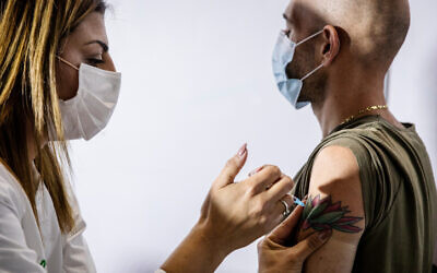 Un Israélien se fait vacciner contre la COVID-19 à Jérusalem, le 4 janvier 2021. (Crédit :  Olivier Fitoussi/Flash90)