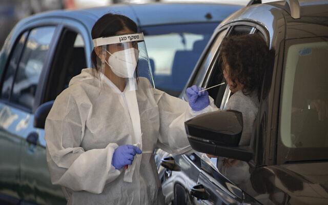 Le personnel soignant pratique des tests de dépistage du coronavirus dans un drive-thru, à Jérusalem, le 4 janvier 2021. (Crédit : Olivier Fitoussi/Flash90)