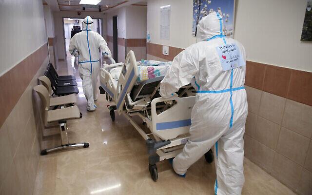 Des employés du centre médical Ziv, dans la ville de Safed, au nord du pays, transportent un nouveau patient dans le service coronavirus, le 7 janvier 2020. (David Cohen/Flash90)