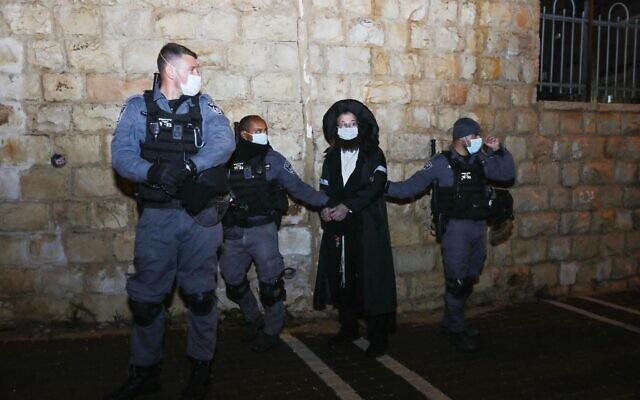 Des policiers arrêtent un homme ultra-orthodoxe lors d'un raid effectué dans le cadre d'un événement illégal en violation des règles de confinement COVID-19, dans la ville de Beit Shemesh, le 20 janvier 2021. (Yaakov Lederman/Flash90)