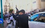 Un policier pointe son arme en l'air lors d'un affrontement avec des émeutiers ultra-orthodoxes qui protestaient contre l'application d'un confinement ordonné en raison du coronavirus, dans la ville de Bnei Brak, le 24 janvier 2021. (Tomer Neuberg/Flash90)