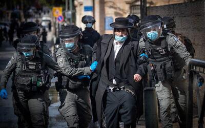 La police affronte des hommes haredim pour faire respecter les restrictions contre le coronavirus, à Jérusalem, le 26 janvier 2021. (Crédit : Yonatan Sindel / Flash90)