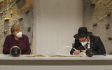 Le rabbin Shaul Nekrich (à droite) et la chancelière allemande Angela Merkel assistent à une cérémonie d'achèvement du rouleau de la Torah de Sulzbach de 1792, redécouvert en 2013 et tout juste restauré, à l'occasion du 76e anniversaire de la libération du camp d'Auschwitz de l'Allemagne nazie, le 27 janvier 2021, Journée internationale de commémoration de l'Holocauste à Berlin. (Crédit : Odd Andersen - Pool/Getty Images)