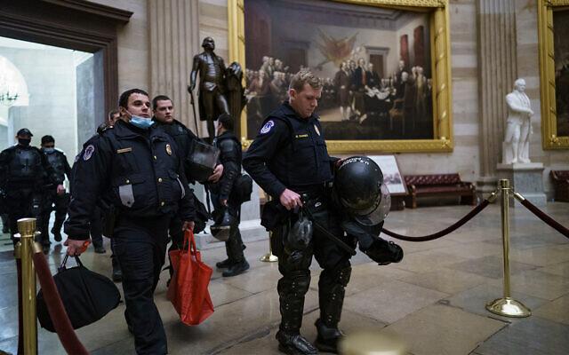 Des officiers de la police du Capitole américain marchent dans la rotonde alors qu'ils répondent, avec d'autres forces de police fédérales, aux violents émeutiers pro-Trump au Capitole à Washington, le 6 janvier 2021. (Crédit : AP Photo/J. Scott Applewhite)