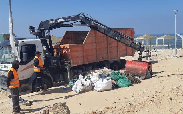 Les employés du ministère de la Protection environnementale nettoient les plages suite à une fuite de pétrole majeure qui a entraîné une marée noire sur la ligne côtière israélienne, le 24 février 2021. (Crédit : ministère de la Protection environnementale)