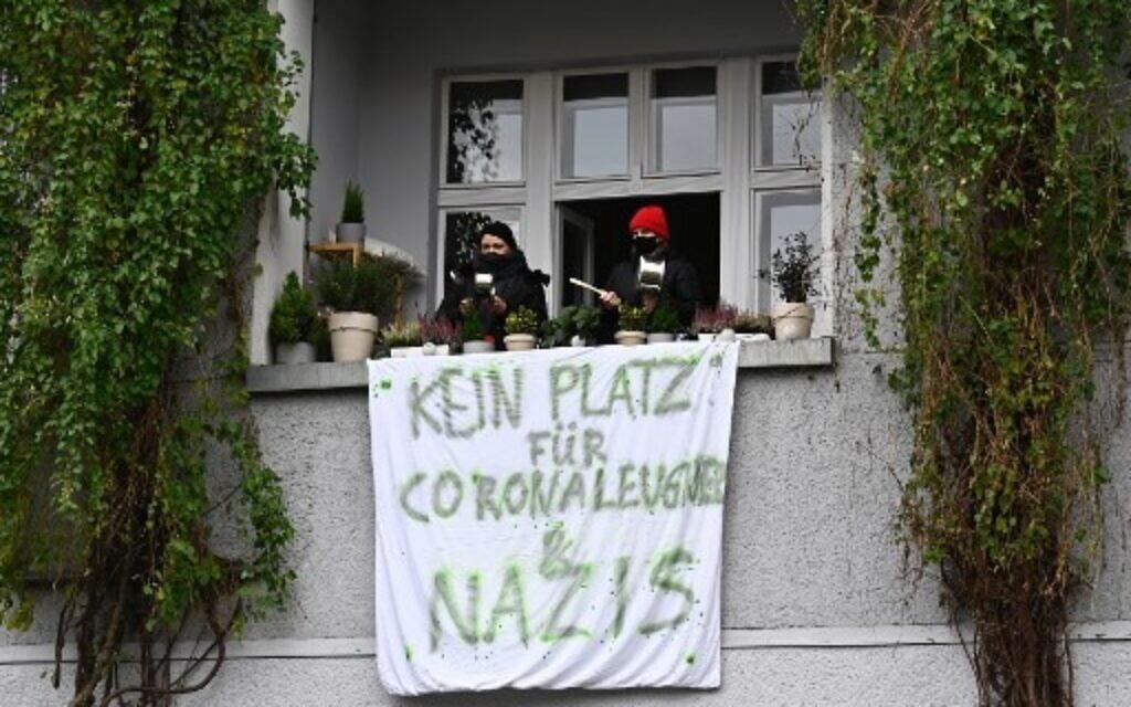 """Des contre-manifestants crient depuis leur balcon où une banderole portant l'inscription """"Pas de place pour les négationnistes et les nazis"""" est fixée lors d'une marche silencieuse contre les mesures visant à freiner la propagation du coronavirus à Berlin, le 22 novembre 2020. (Tobias Schwarz / AFP)"""
