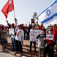 Un groupe de militants birmans résidant en Israël brandissent (de gauche à droite) le drapeau historique de la Birmanie (jusqu'en 1974), le drapeau du parti de la Ligue nationale pour la démocratie de la dirigeante évincée Aung San Suu Kyi, et le drapeau d'Israël, lors d'une manifestation devant l'ambassade du pays dans la ville côtière méditerranéenne de Tel Aviv, le 3 février 2021. (JACK GUEZ / AFP)