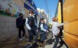 Des élèves jordaniens montent dans un bus pour rentrer chez eux après avoir assisté à un cours pour la première fois depuis près d'un an, à Amman, le 7 février 2021. (Crédit : Khalil MAZRAAWI / AFP)