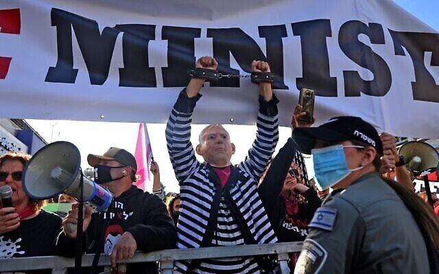 Des manifestants anti-Netanyahu devant le tribunal de district de Jérusalem, alors que le Premier ministre Benjamin Netanyahu arrive pour son procès au tribunal de district, le 08 février 2021 (Crédit : Emmanuel DUNAND/AFP)