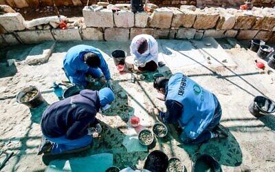 Des travailleurs employés dans le cadre d'un projet pilote mené par l'agence culturelle des Nations unies, l'UNESCO, restaurent le 9 février 2021 le sol en mosaïque d'un ancien complexe d'églises, dans la petite ville de Rihab, à 70 kilomètres au nord d'Amman. (Crédit : Khalil MAZRAAWI / AFP)